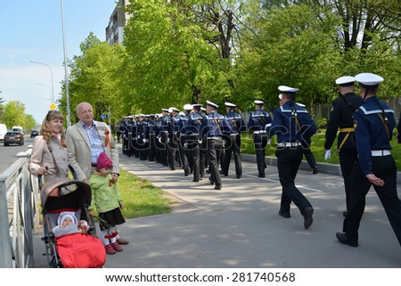KALININGRAD, RUSSIA - MAY 09, 2015: The elderly man with the daughter and granddaughters look at a system of military seamen after parade in honor of the Victory Day