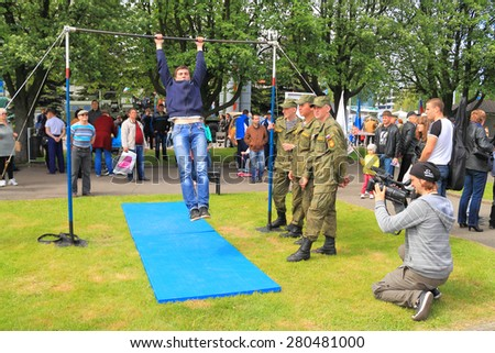"KALININGRAD, RUSSIA - MAY 16, 2015: Videographer filmed as a soldier performs an exercise on the bar. Action ""service contract in the Armed Forces - your choice!"" In Kaliningrad"