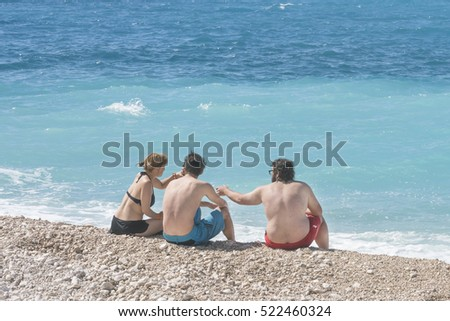 Kalkan, Turkey, May 5, 2016: Group of people sitting on the beach near the sea