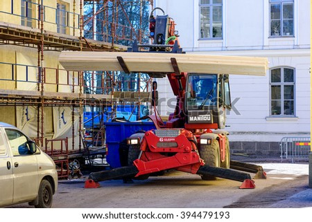 Kalmar, Sweden - March 17, 2016: A Manitou forklift with support legs out hold a bunch of planks next to some scaffoldings outside a building.