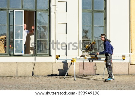 Kalmar, Sweden - March 17, 2016: One young adult outside the window handle a motorized miter saw and hand over the sawed plank to a person on the inside. DeWalt logo on saw.