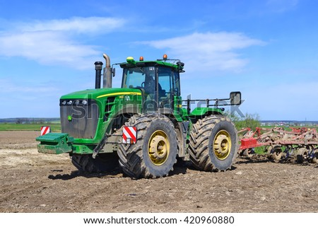 Kalush, Ukraine - April 16: A modern  John Deere  tractor on the spring field works near  the town Kalush, Western Ukraine April 16, 2016