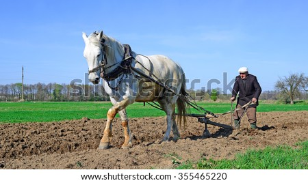 Kalush, Ukraine â?? April 23: Fallowing of a spring field by a manual plow on horse-drawn  near the town Kalush, Western Ukraine April 23, 2015 - stock photo