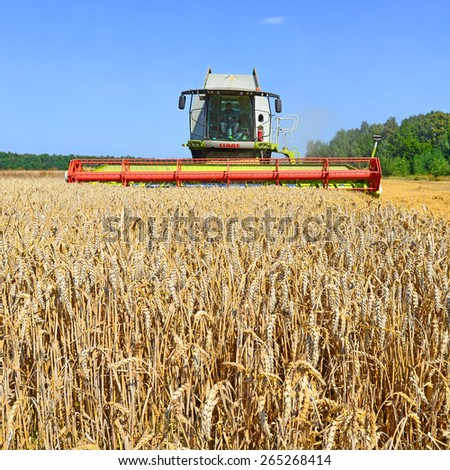 Kalush, Ukraine - AUGUST 11: Modern  combine harvesting grain in the field near the town Kalush, Western Ukraine August t1, 2014 - stock photo