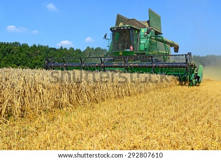 Kalush, Ukraine - AUGUST11: Modern e combine harvesting grain in the field near the town Kalush, Western Ukraine August 11, 2014
