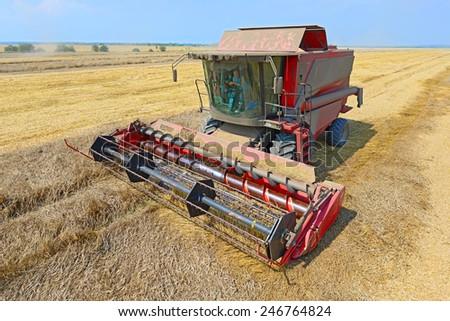 Kalush, Ukraine - AUGUST 10: Modern John Deere combine harvesting grain in the field near the town Kalush, Western Ukraine August 10, 2014  - stock photo