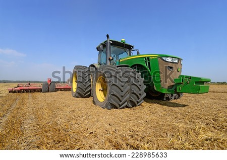Kalush, Ukraine - AUGUST 4: Modern John Deere tractor in the field near the town Kalush, Western Ukraine AUGUST 4, 2014