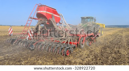 Kalush, Ukraine - August 10 : Modern John Deere tractor with a planter in the field near the town Kalush, Western Ukraine August 10, 2014 - stock photo