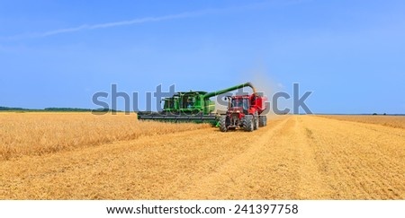 Kalush, Ukraine - AUGUST 7: Modern  tractor with a tank for transportation of grain near the combines harvesting. in the field near the town Kalush, Western Ukraine August 7, 2013.  - stock photo