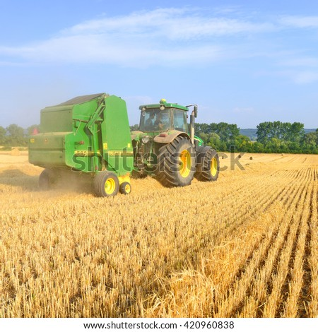 Kalush, Ukraine - August 13: Universal tractor harvesting straw in the field near the town Kalush, Western Ukraine August 13, 2015