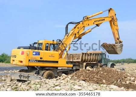 Kalush, Ukraine - July 8: Loading gravel in the car body on the construction of a protective dam near the town of Kalush, Western Ukraine July 8, 2015