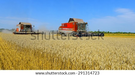 Kalush, Ukraine - July 8: Modern  combines harvesting grain in the field near the town Kalush, Western Ukraine July 8, 2014