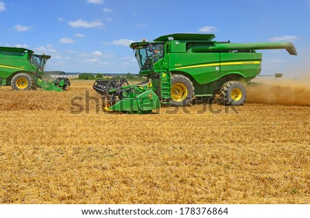 Kalush, Ukraine - July 9: Modern John Deere combines harvesting grain in the field near the town Kalush, Western Ukraine July 9, 2013