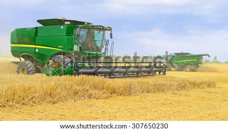Kalush, Ukraine - July 17: Moderns John Deere combines harvesting grain in the field near the town Kalush, Western Ukraine July 17, 2015 - stock photo