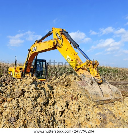 Kalush, Ukraine � October 7: Modern JCB excavator on the highway pipeline performs excavation work in the field near the town Kalush, Western Ukraine October 7, 2014