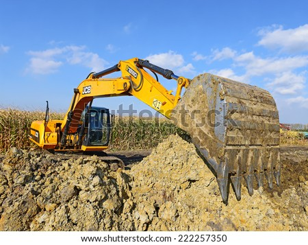 Kalush, Ukraine - October 7: Modern JCB excavator on the highway pipeline performs excavation work in the field near the town Kalush, Western Ukraine October 7, 2014