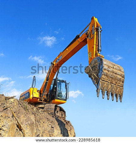 Kalush, Ukraine  October 7: Modern JCB excavator on the highway pipeline performs excavation work in the field near the town Kalush, Western Ukraine October 7, 2014 - stock photo
