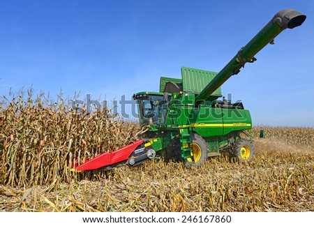 Kalush, Ukraine � OCTOBER 8: Modern John Deere combine harvesting corn  in the field near the town Kalush, Western Ukraine October 8, 2013 - stock photo