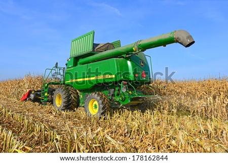 Kalush, Ukraine - OCTOBER 8: Modern John Deere combine harvesting corn  in the field near the town Kalush, Western Ukraine October 8, 2013 - stock photo