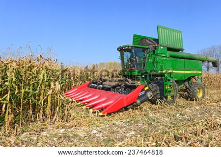 Kalush, Ukraine  OCTOBER 14: Modern John Deere combine harvesting corn  in the field near the town Kalush, Western Ukraine October 14, 2014 - stock photo