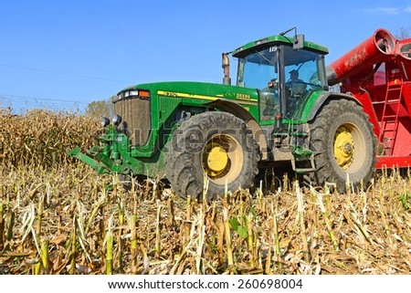 Kalush, Ukraine â?? OCTOBER 14: Modern John Deere tractor with a trailer to transport the grain to harvest corn  in the field near the town Kalush, Western Ukraine October 14, 2014 - stock photo