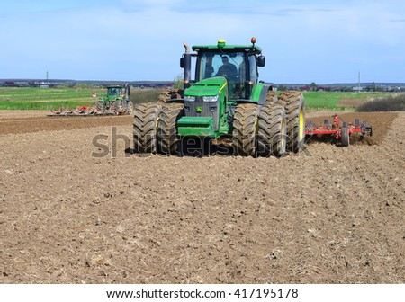 Kalush, Ukraine - Ukraine April 16: Modern John Deere tractor on soil treated cultivator in the field near the town Kalush, Western Ukraine April 16, 2016 - stock photo