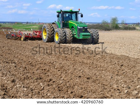 Kalush, Ukraine - Ukraine April 16: Modern John Deere tractor on soil treated cultivator in the field near the town Kalush, Western Ukraine April 16, 2016