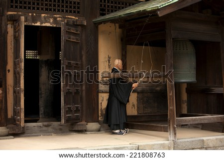 KAMAKURA, JAPAN - MARCH 23, 2009: Buddhist monk rings a bell before a prayer in a monastery in Kamakura.