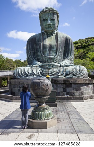 KAMAKURA, JAPAN - MAY 23 : A woman prays in front of the Daibutsu Great Buddha at Kotoku-in temple in Kamakura, Japan on 23rd May 2012. The bronze Buddha dates from the 13th century and is 13.3m high.