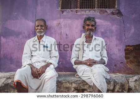 KAMALAPURAM, INDIA - 02 FABRUARY 2015: Local indian men siiting in front of home in a town close to Hampi. Post-processed with grain, texture and colour effect.