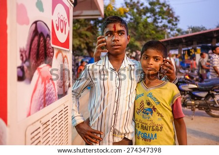 KAMALAPURAM, INDIA - 02 FEBRUARY 2015: Two Indian brothers hugging in street and fooling around with people around them - stock photo