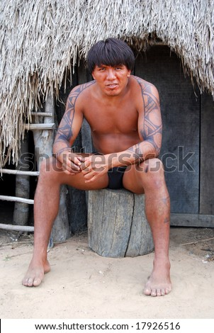 KAMAYURA VILLAGE, BRAZIL - MAY 18: The Kamayura is a threatened Indian tribe of under 400 people. A man sitting at doorway of a hut on May 18, 2008, in Kamayura village. - stock photo
