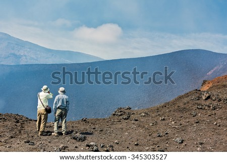 KAMCHATKA, RUSSIA - AUGUST 28, 2013: Tourists go on a route through the active lava flow from a new crater on the slopes of volcanoes Tolbachik