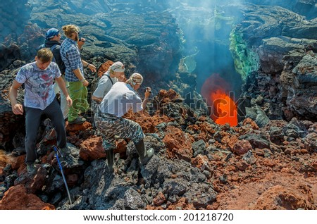 KAMCHATKA, RUSSIA - AUGUST 28, 2013: Tourists visiting the output of molten lava on the active lava flow from a new crater on the slopes of volcanoes Tolbachik, on background volcano Ostry Tolbachik - stock photo