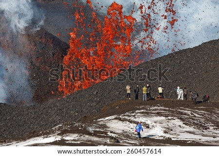 KAMCHATKA, RUSSIA - FEBRUARY 2, 2013: Eruption Tolbachik Volcano on Kamchatka, tourists on background fountain of lava escaping from the crater of the volcano. Russia, Far East, Kamchatka Peninsula. - stock photo