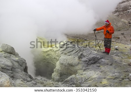 KAMCHATKA, RUSSIA - JULY, 18. A tourist observes an active fumarole, producing volcanic gas. July 18, 2015 in Kamchatka, Russia. - stock photo