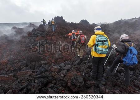 KAMCHATKA, RUSSIA - JULY 27, 2013: Group of tourists hiking on the lava field eruption Tolbachik Volcano on Kamchatka Peninsula (Klyuchevskaya Group of Volcanoes.). Eurasia, Russia, Far East. - stock photo