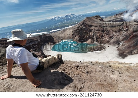 KAMCHATKA, RUSSIA - JULY 21, 2013: Tourists sitting on the edge of crater of active Gorely Volcano watching at volcanic landscape of Kamchatka Peninsula. Eurasia, Russia, Far East. - stock photo