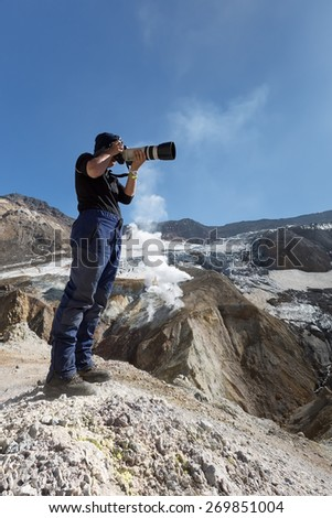KAMCHATKA, RUSSIA - SEPTEMBER 11, 2013: Photographer takes a picture in the crater of active Mutnovsky Volcano (Mutnovka). Kamchatka, Russia. - stock photo