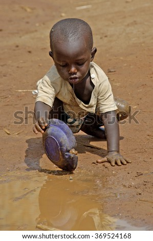 Kampala, Uganda-10 April 2007: Thirsty and hungry child is trying to get some water in a dirty pool. - stock photo