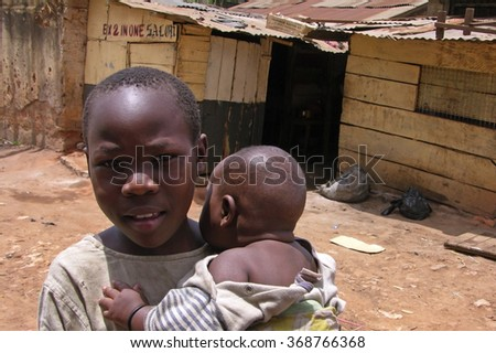 Kampala, Uganda-10 April 2007: Young boy is carrying his little brother in front of his village near Kampala town.