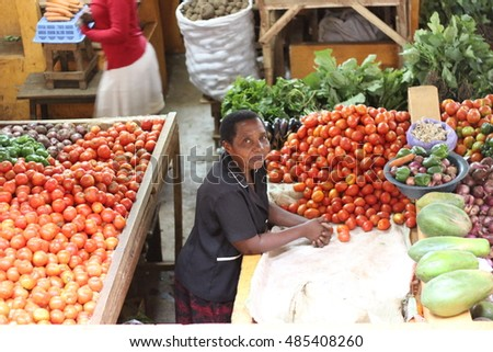 KAMPALA, UGANDA - CIRCA NOVEMBER 2015: Ugandans selling and buying fresh local products, including vegetables, at a busy indoor market in the capital city Kampala.