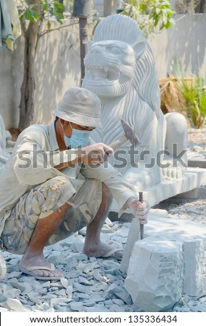 KAMPONG THUM CAMBODIA MARCH 26: A carver using a chisel on a block of marble to carve a statue Buddha's on march 26 2013 in Kampong Thum Cambodia.
