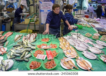 Kanazawa, Japan - April 14, 2014: A fish vendor in Omicho Market. Omicho Ichiba has been Kanazawa's largest fresh food market since the Edo Period. Today, it is a busy network of covered streets. - stock photo