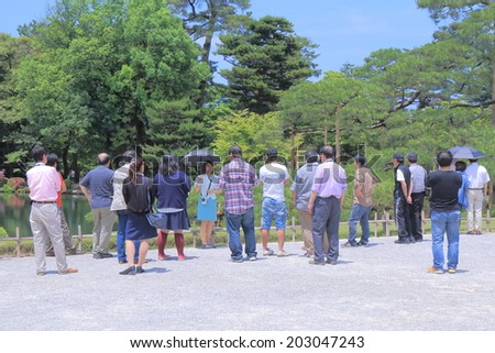 KANAZAWA JAPAN - 6 JUNE, 2014: A tour guide explains about Kenrokuen Garden. Kenrokuen is an old private garden and is one of the Three Great Gardens of Japan.