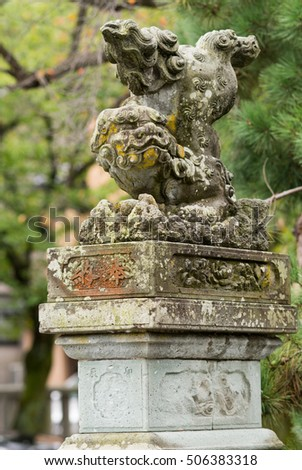 Kanazawa, Japan - September 22, 2016: Old stone Japanese Lion-monster statue at Kenrokuen Garden functions as guardian. Beast throws back legs in air. Moss and yellow mold. Green foliage in back.