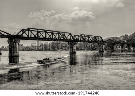 KANCHANABURI, THAILAND � FEBRUARY 2: Tour boat cruises below the bridge on the river Kwai in Kanchanaburi, Thailand on February 2, 2009. The bridge is famous due to a movie and its history in WW2. - stock photo