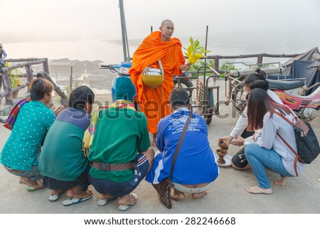 KANCHANABURI, THAILAND - JAN 19, 2015 : Unidentified tourists offering rice to Buddhist monk in the morning on January 19, 2015 at Sangklaburi, Kanchanaburi, Thailand. - stock photo