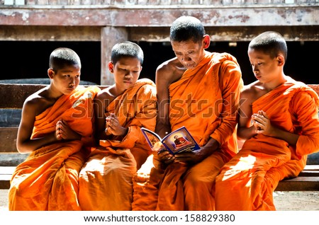 KANCHANABURI THAILAND-January 29:  An unidentified monk teach young novice monks 12-15 years old in temple on January 29, 2012 in KANCHANABURI THAILAND. Temple is the school  in rural of Thailand.    - stock photo