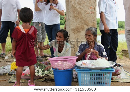 Kanchanaburi, Thailand - July 22, 2013: Unidentified people sell flowers to tourists at Wat Saam Prasob, the last remaining vestige of the old town flooded for the creation of Khao Laem Reservoir.